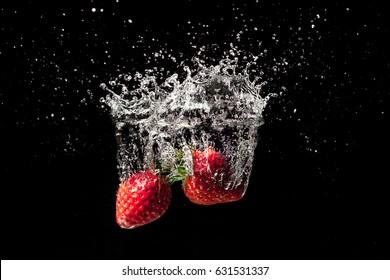 Strawberry fruit creating a beautiful splash underwater with black background
