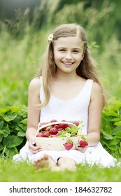 Strawberry, fruit garden - young girl with picked strawberries in the garden