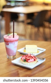 strawberry fruity frappe and cheese cake and strawberry tart. food and bekery in cafe. blur bokeh background is table and chairs