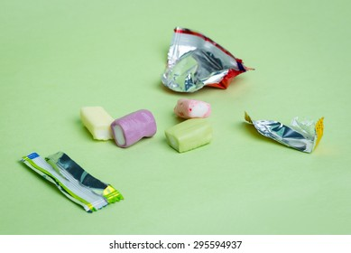 Strawberry, grape, banana and green apple chewy candies and their open wrappers on a green background.