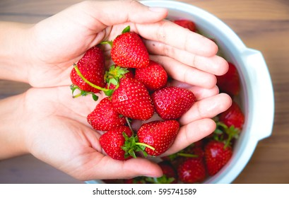 Strawberry in hand and a bowl on wooden background