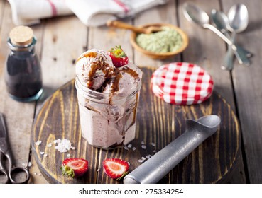 Strawberry ice cream with balsamic vinegar and fennel seeds on a wooden background