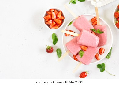 Strawberry ice cream popsicles on white plate over white stone background with free text space. Top view, flat lay