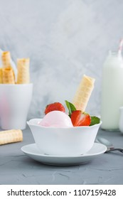 Strawberry ice cream in white plate with berrys and wafer tubule, glass with waffers, bottle of milk, metallic spoons on grey concrete background. Vertical orientation.