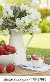 Strawberry and ice-cream on a wooden table in the open air; a jasmin Bouquet on a table