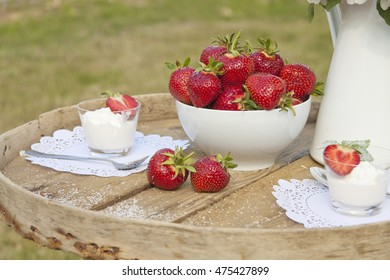 Strawberry and ice-cream on a wooden table in the open air