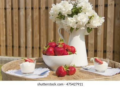 Strawberry and ice-cream on a wooden table in the open air; a jasmin Bouquet on a table; a wooden fence on a background