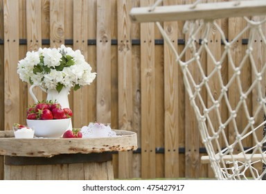 Strawberry and ice-cream on a wooden table in the open air; a jasmin Bouquet on a table; a wooden fence on a background; Dessert near a hammock