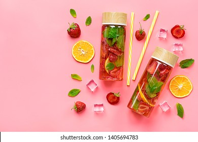 Strawberry infused water, cocktail, lemonade or tea. Summer iced cold drink with strawberry, lemon and leaf of mint on pink background. Flat lay. Top view.