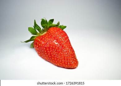 Strawberry isolated, white clipping path, with green leaf, closeup, macro photo