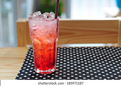 Strawberry italian soda on wood table with black polka dot tablecloth.