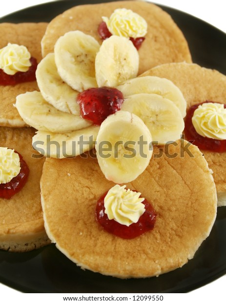Strawberry jam and butter pancakes with sliced banana.