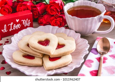 Strawberry jam filled heart shaped sugar cookies with red roses and pink cup filled with hot tea