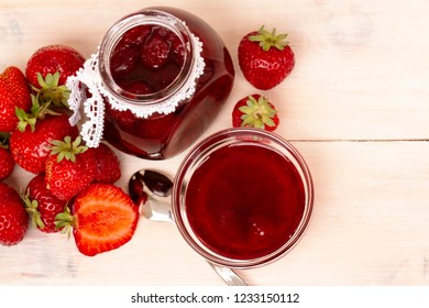 Strawberry jam with fresh strawberries on white wooden background. Glass jar and bowl with delicious strawberry confiture. Fresh homemade strawberry jam with berries in small jar and spoon. top veiw