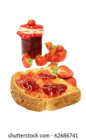 Strawberry jam on a toast for breakfast with fresh fruits and jar
