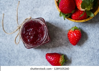 Strawberry jam or preserve in a jar and strawberrieson the side basket, selective focus