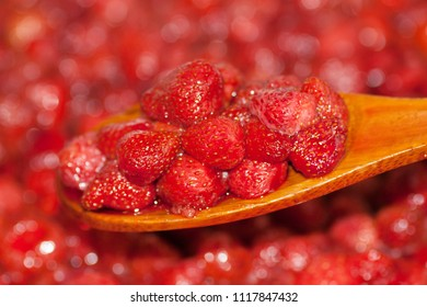 Strawberry jam is stirred with a spoon. Fruit dessert close up.