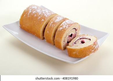 Strawberry jam swiss roll dessert on square plate , disposable paper tablecloth background