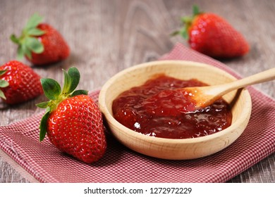 strawberry jam in wooden cup on wooden table