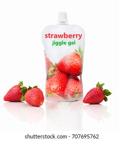 "Strawberry jiggle gel with ""strawberry jiggle gel"" writing. Isolated on white background with shadow reflection. Strawberry fruit pouch for kids. Fruit packet for babies with fresh strawberries."