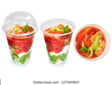 Strawberry, kiwi with yogurt in a disposable plastic cup, isolated on white background