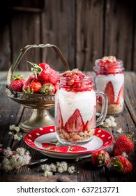 Strawberry layer dessert in the glass jar or mug on the old wooden background