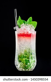 Strawberry layered Mojito isolated at black background. Strawberry mojito is a cocktail with mint, strawberry syrup, soda, lime, white rum and ice crush