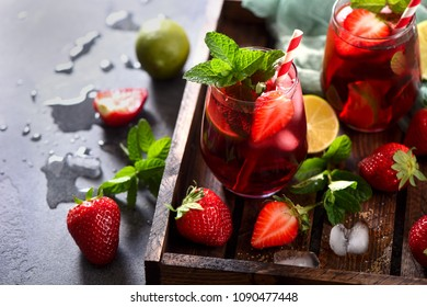 Strawberry lemonade drink, refreshing summer mojito with strawberries, lime and mint