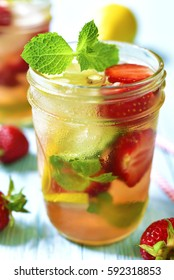 Strawberry lemonade with lemon and mint in a mason jar on a blue wooden table.Summer recipe.