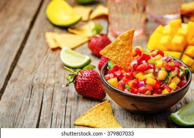 strawberry mango pepper salsa on a dark wood background. toning. selective focus