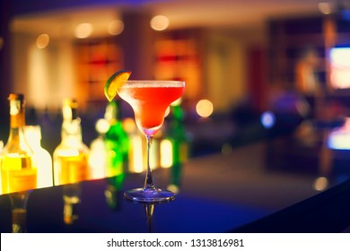 Strawberry margarita cocktail on night bar background