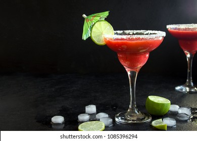 Strawberry Margarita or Daiquiri Cocktail with lime on black background, copy space. Frozen homemade strawberry summer cocktail.
