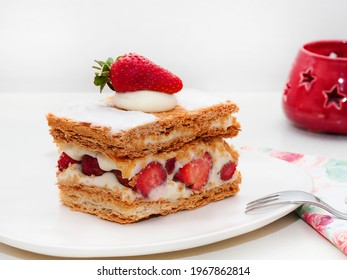 Strawberry milfoy, mille-feuille, a pastry containing layers of puff pastry, pastry cream and powdered sugar. Strawberry pie or cake, in a white plate.