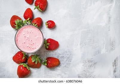 Strawberry milkshake with berries, food background, top view