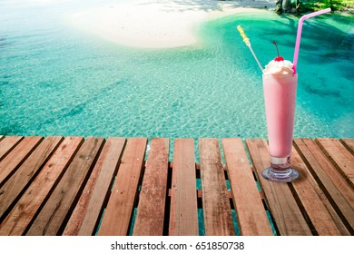 Strawberry milkshake drink on the beach background good for refreshing in Summer vacation day.