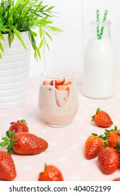 Strawberry milkshake with fresh strawberries and a jug of milk