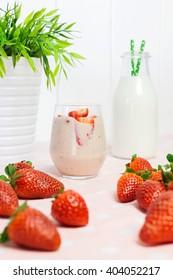Strawberry milkshake with fresh strawberries and a jug of milk