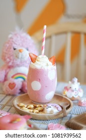 Strawberry milkshake. A glass of strawberry smoothy and a pink teddy bear on the background. Sweet pink party for little girl birthday party.