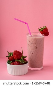 Strawberry milkshake with a pink straw and strawberries on a glass on a pink background. Healthy food and diet concept