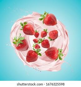 Strawberry milkshake splashing with fruits, on blue background