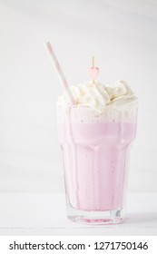 Strawberry milkshake with whipped cream on a white background, copy space for text. Valentine's day concept.