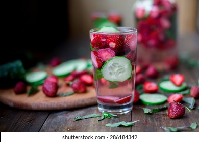 strawberry mint cucumber infused water decorated in rustic style on dark wood table background