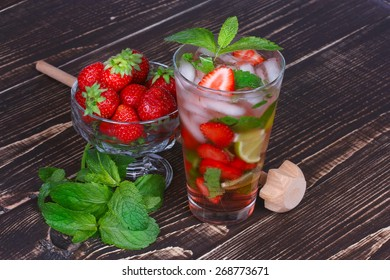 Strawberry mojito cocktail on wooden background