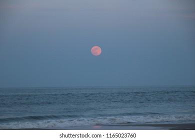 Strawberry moon over beach on summer night.