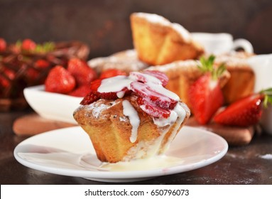 Strawberry muffin with melted ice cream on a white porcelain plate. These delicious low fat treats are perfect for a summer treat