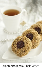 Strawberry oatmeal thumbprint cookies with a cup of tea in the background