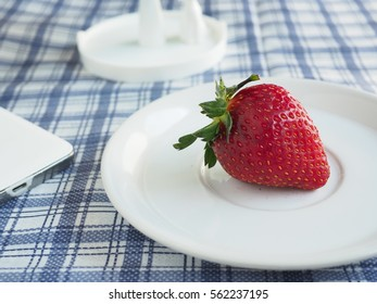 A strawberry on dish