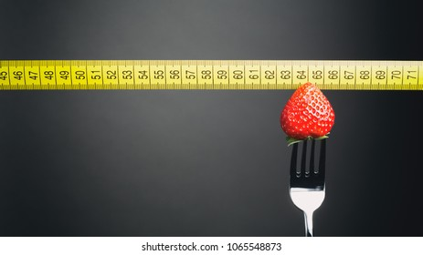 Strawberry on a fork indicating body weight on a yellow measuring tape. Copy space available.