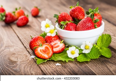 Strawberry. Strawberry on wood background. Red strawberries, strawberries . Strawberry with green leaves. Healthy strawberries. strawberry flower.