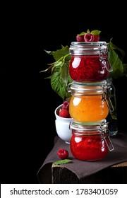 Strawberry, orange and raspberry jams in glass jars against the black background. Three jars of jam on the edge of the table